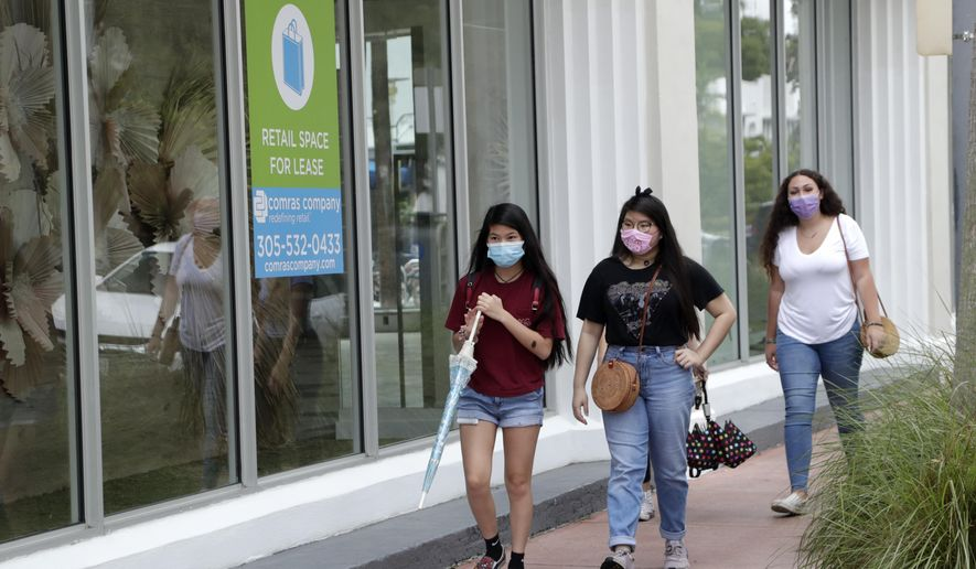 Shoppers wear protective face coverings as they walk past a vacant retail store for lease at Lincoln Road Mall during the new coronavirus pandemic, Wednesday, June 17, 2020, in Miami Beach, Fla. (AP Photo/Lynne Sladky)