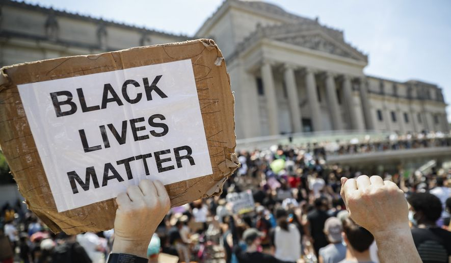 "A protester holds a sign that reads ""BLACK LIVES MATTER"" during a Juneteenth rally outside the Brooklyn Museum, Friday, June 19, 2020, in the Brooklyn borough of New York. Juneteenth commemorates when the last enslaved African Americans learned they were free 155 years ago. Now, with support growing for the racial justice movement, 2020 may be remembered as the year the holiday reached a new level of recognition. (AP Photo/John Minchillo)"