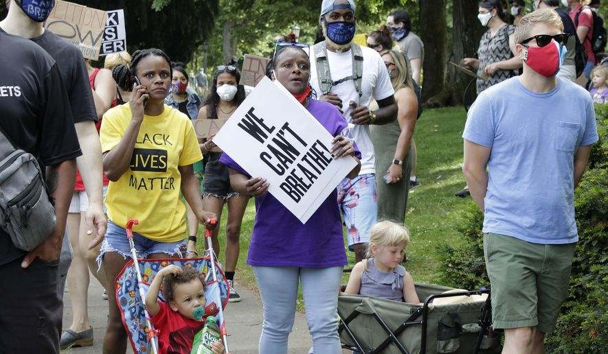A woman pushes a stroller holding her son at a Juneteenth rally and march through a historically Black neighborhood in Portland, Oregon. (AP Photo/Gillian Flaccus)  ** FILE **
