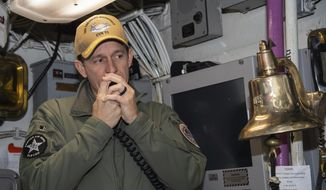 In this image provided by the U.S. Navy, Capt. Brett Crozier, then-commanding officer of the aircraft carrier USS Theodore Roosevelt (CVN 71), addresses the crew on Jan. 17, 2020, in San Diego, Calif. In a stunning reversal, the Navy has upheld the firing of Crozier, the aircraft carrier captain who urged faster action to protect his crew from a coronavirus outbreak, according to a U.S. official.  (Mass Communication Specialist Seaman Alexander Williams/U.S. Navy via AP)