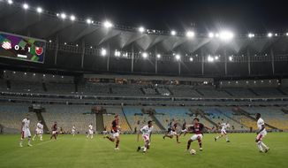 Players of Bangu, wearing white uniforms, and Flamengo play a Rio de Janeiro soccer league match at the Maracana stadium in Rio de Janeiro, Brazi, Thursday, June 18, 2020. Rio de Janeiro's soccer league resumed after a three-month hiatus because of the coronavirus pandemic. The match is being played without spectators to curb the spread of COVID-19. (AP Photo/Leo Correa)