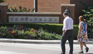 FILE - In this Sept. 29, 2015, file photo, two people walk past one of the entrances to the Chesapeake Energy Corporation campus in Oklahoma City.   On Friday, June 19, 2020, Chesapeake Energy, the struggling shale gas driller which was once one of the largest natural gas producers in the U.S., has missed $13.5 million in interest payments. The Oklahoma City-based company owes nearly $9 billion to its creditors.  (AP Photo/Sue Ogrocki, File)