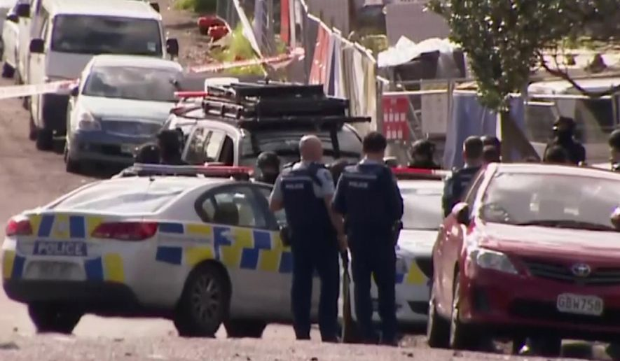 This image made from a video, shows armed police at the scene of a shooting incident following a routine traffic stop in Auckland, New Zealand, Friday, June 19, 2020. New Zealand police say a few officers have been shot and seriously injured and a suspect is on the run. (TV New Zealand via AP)