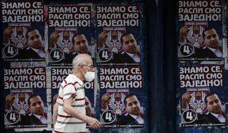 """In this photo taken on Tuesday, June 16, 2020, a man wearing a face mask to protect against coronavirus, passes by election posters showing Serbian Right leader Misa Vacic, that reads: """"We know each other well, we grew up together!"""", in Belgrade, Serbia. Serbia is holding a parliamentary vote this weekend that takes place amid concerns over the continuing spread of the new coronavirus and political divisions in the Balkan country. (AP Photo/Darko Vojinovic)"""