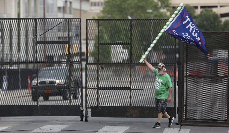 Mike Pellerin waves a Donald Trump campaign flag near a barricade in downtown Tulsa, Okla., ahead of President Donald Trump's Saturday's campaign rally Friday, June 19, 2020. (Mike Simons/Tulsa World via AP)