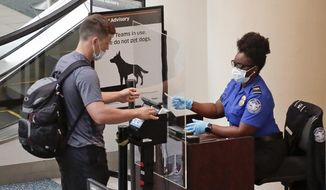 FILE - In this June 17, 2020 file photo, a TSA worker, right, checks a passenger before entering a security screening at Orlando International Airport  in Orlando, Fla.   A high-ranking Transportation Security Administration official says the agency is falling short when it comes to protecting airport screeners and the public from the new coronavirus, according to published reports. A federal office that handles whistleblower complaints has ordered an investigation.  (AP Photo/John Raoux, File)