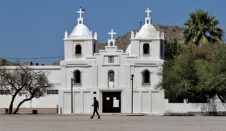In this June 13, 2020, photo, a man walks past Our Lady of Guadalupe church in Guadalupe, Ariz. As the coronavirus spreads deeper across America, it's ravaging through the homes and communities of Latinos from the suburbs of the nation's capital to the farm fields of Florida to the sprawling suburbs of Phoenix and countless communities in between. (AP Photo/Matt York)