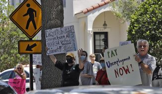 Protestors wave signs at Florida Gov. Ron DeSantis as he and Vice President Mike Pence visit the Westminster Baldwin Park Wednesday, May 20, 2020, in Orlando, Fla. Pence and DeSantis also participated in a roundtable discussion with hospitality and tourism industry leaders to discuss their plans for re-opening during the coronavirus outbreak. (AP Photo/Chris O'Meara)