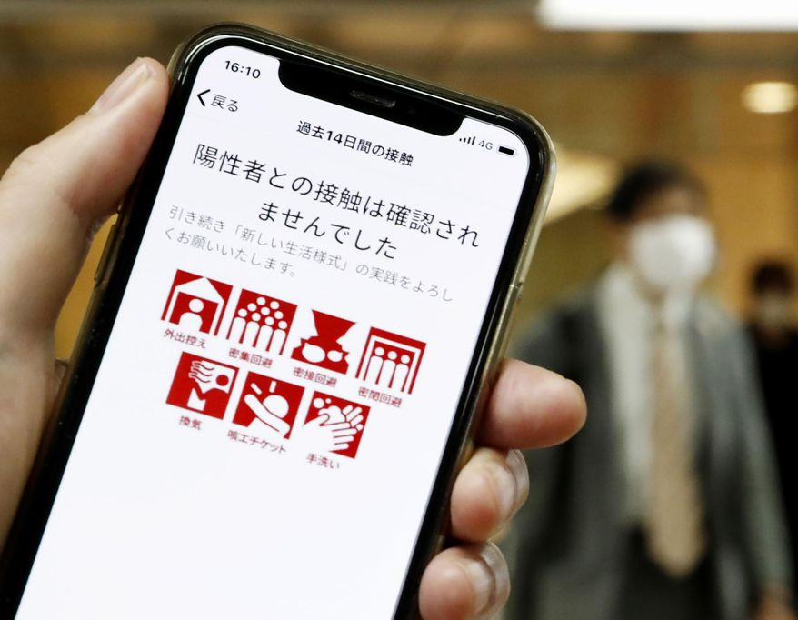 """The smartphone screen, seen in Tokyo, Japan, shows a trial version of the COVID-19 Contact Confirming Application, or COCOA, released Friday, June 19, 2020, by the Ministry of Health, Labor and Welfare. The notice says """"There was no close contact."""" The coronavirus tracing app is designed to alert users if they come in contact with someone tested positive for the coronavirus.  Once installed, the app logs data via Bluetooth from phones that stay in close proximity for over 15 minutes.(Kyodo News via AP)"""