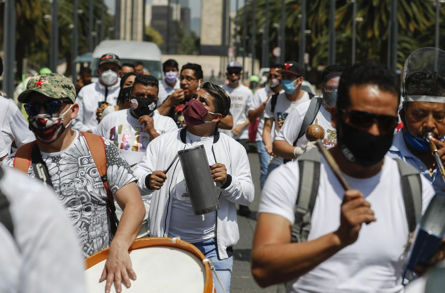 Musicians play their instruments during a protest demanding financial support after not being able to earn a living since March because of the restrictions to curb the spread of the new coronavirus, in Mexico City, Friday, June 19, 2020. (AP Photo/Eduardo Verdugo)