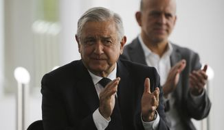Mexico's President Andres Manuel Lopez Obrador, left, applauds prior to delivering a speech during his visit to a public hospital in Cuernavaca, Mexico, Friday, June 19, 2020.  Lopez Obrador is desperate to restart Mexico's struggling economy after being cooped up under social distancing measures due to the new coronavirus pandemic. (AP Photo/Fernando Llano)