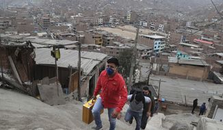 Josue Yacahuanca, a 21-year-old barber, his briefcase of tools in hand, ascends a flight of stairs in the San Juan de Lurigancho neighborhood of Lima, Peru, Friday, June 19, 2020. In the midst of one of the worst recessions in the western hemisphere due to an extensive quarantine to curb the spread of the new coronavirus, the barber offers free haircuts in Lima's working class neighborhoods. (AP Photo/Martin Mejia)