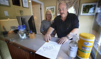"""In this Wednesday, June 10, 2020, photo, Cod Cove Inn owners Ted and Jill Hugger show a draft of a compliance form that inn owners may be required to have out-of-state guests sign before being allowed to check in at their inn in Edgecomb, Maine. The form is part of the """"Keep Maine Healthy"""" plan the state is proposing to help prevent the spread of the coronavirus. Residents of New Hampshire and Vermont would be exempt. (AP Photo/Robert F. Bukaty)"""