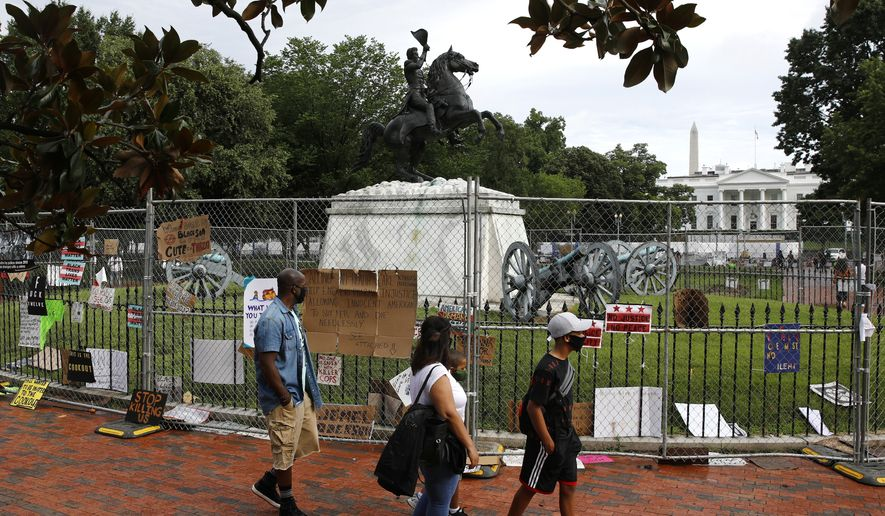 People wear face masks to protect against the spread of the new coronavirus as they walk past protest signs affixed to fencing surrounding a statue of President Andrew Jackson in Lafayette Park near the White House in Washington, Saturday, June 20, 2020. (AP Photo/Patrick Semansky)