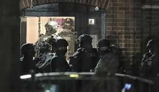 """Armed police officers investigate at a block of flats off the Basingstoke Road in Reading after an incident at Forbury Gardens park in the town centre of Reading, England, Saturday, June 20, 2020. Several people were injured in a stabbing attack in a park in the English town of Reading on Saturday, and British media said police were treating it as """"terrorism-related."""" (Steve Parsons(PA via AP)"""