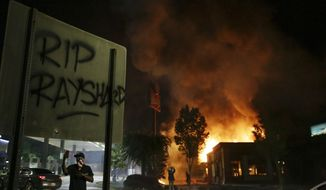 "In this Saturday, June 13, 2020, file photo, ""RIP Rayshard"" is spray-painted on a sign as flames engulf a Wendy's restaurant during protests in Atlanta. The restaurant was where Rayshard Brooks was shot and killed by police the previous evening following a struggle in the restaurant's drive-thru line. (AP Photo/Brynn Anderson, File)"