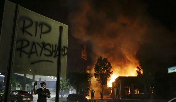 """In this Saturday, June 13, 2020, file photo, """"RIP Rayshard"""" is spray-painted on a sign as flames engulf a Wendy's restaurant during protests in Atlanta. The restaurant was where Rayshard Brooks was shot and killed by police the previous evening following a struggle in the restaurant's drive-thru line. (AP Photo/Brynn Anderson, File)"""