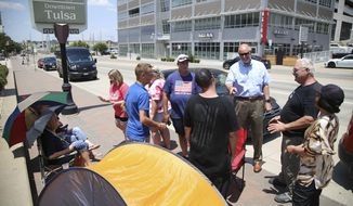 FILE - In this June 15, 2020, file photo Donald Trump supporters gather outside the BOK Center in Tulsa, Okla. Trump's campaign says six staff members helping set up for his Saturday night rally in Tulsa, Oklahoma, have tested positive for coronavirus. (Matt Barnard/Tulsa World via AP, File