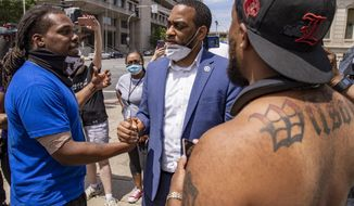 HOLD FOR STORY- In this June 17, 2020 photo U.S. Senate candidate Charles Booker shakes hands with protestors in Louisville, KY. Booker is running against Amy Grath for the senate democratic nomination. (Alton Strupp/Louisville Courier Journal via AP)