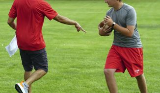 In this photo taken June 15, 2020, Albuquerque Academy Football offensive coordinator coach Zachary Haas, left, works on drills with quarterback Mark McIntosh during practice in Albuquerque, N.M. New Mexico prep sports in slowly returning following restrictions from the novel coronavirus. (Adolphe Pierre-Louis/The Albuquerque Journal via AP)