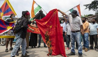 Exile Tibetans and local Indians burn a Chinese national flag during a protest in Dharmsala, India, Friday, June 19, 2020. India said Thursday it was using diplomatic channels with China to de-escalate a military standoff in a remote Himalayan border region where 20 Indian soldiers were killed this week. (AP Photo/Ashwini Bhatia)