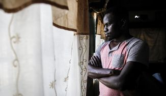 In this photo taken Thursday, June 11, 2020, Martin Okello looks out of the window in the house he shares with other Ugandan LGBT refugees in Nairobi, Kenya. He and other members of the LGBT community in East Africa face discrimination that has forced many to flee their home countries for Kenya, which has become a haven for them. It is the only East African nation where someone can seek asylum and be registered as a refugee based on their LGBT status. Yet even in Kenya, they can be encounter discrimination and violence, and the country still criminalizes gay sex. (AP Photo/Brian Inganga)