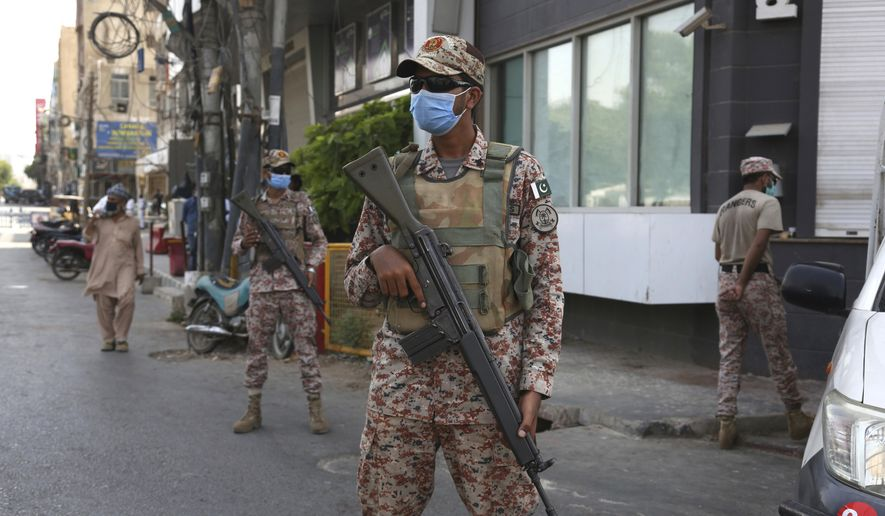Soldiers stand alert outside a restricted area that is sealed off to control the spread of the coronavirus, in Karachi, Pakistan, Friday, June 19, 2020. (AP Photo/Fareed Khan)