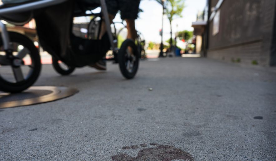 A bare bloody footprint remains on the sidewalk in the 2900 block of Hennepin Avenue after an early morning shooting, Sunday, June 21, 2020, in Minneapolis' Uptown neighborhood. The shooting in the popular nightlife area early Sunday left one man dead and multiple people wounded in a chaotic scene that sent people ducking into restaurants and other businesses for cover. (Jerry Holt/Star Tribune via AP)