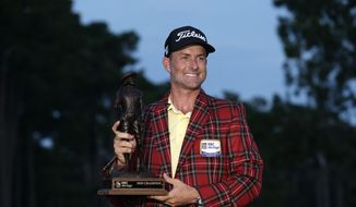 Webb Simpson holds the championship trophy after winning the RBC Heritage golf tournament, Sunday, June 21, 2020, in Hilton Head Island, S.C. (AP Photo/Gerry Broome)