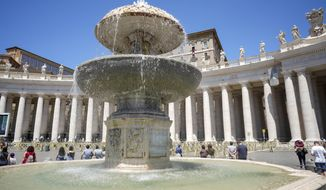Pope Francis, framed by one the fountains that adorn St' Peter's Square, delivers his blessing as he recites the Angelus noon prayer from the window of his studio overlooking St.Peter's Square, at the Vatican, Sunday, June 21, 2020. (AP Photo/Andrew Medichini)