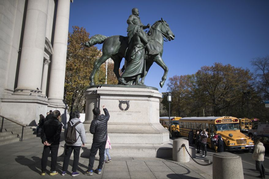 In this Nov. 17, 2017, file photo, visitors to the American Museum of Natural History in New York look at a statue of Theodore Roosevelt, flanked by a Native American man and African American man. The statue will be coming down after the museum's proposal to remove it was approved by the city. (AP Photo/Mary Altaffer, File)