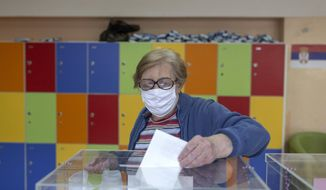 A woman casts her ballot at a polling station in Belgrade, Serbia, Sunday, June 21, 2020. Serbia's ruling populists are set to tighten their hold on power in a Sunday parliamentary election held amid concerns over the spread of the coronavirus in the Balkan country and a partial boycott by the opposition. (AP Photo/Marko Drobnjakovic)