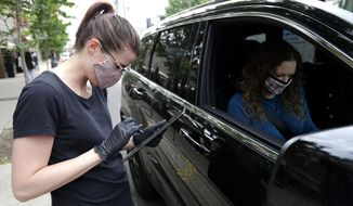 Michaela Kelly, left, a staffer from Alinea restaurant, checks carryout orders with a customer in Chicago, Saturday, June 20, 2020. Due to the coronavirus, Alinea shifted to carryout on March 17. Since then, it has served 82,000 meals, said Nick Kokonas, the restaurant's co-owner. Kokonas said carryout was so successful that Alinea hired all its employees back by the end of April at 80% of their former pay and benefits.  (AP Photo/Nam Y. Huh)