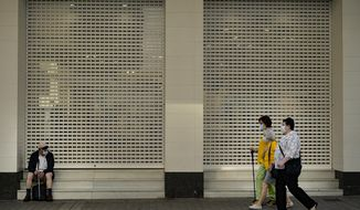A group of women walk past beside a man seated while wearing face mask to prevent the coronavirus during the last day of the lockdown, in Pamplona, northern Spain, Saturday, June 20, 2020. (AP Photo/Alvaro Barrientos)