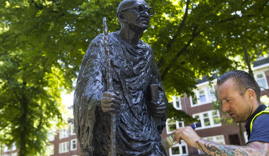 """A worker applied a coat of wax to the bronze statue of Mahatma Gandhi after removing red paint in Amsterdam Wednesday, June 17, 2020. The statue was daubed in red paint and """"Racist"""" was written on its base, an apparent reference to Gandhi's racist controversial references to Africans in his writings, amid a wave of attacks on statues of historical figures in the United States and Europe. The death of George Floyd at the hands of Minneapolis police officers has sparked a reexamination of many countries' colonial histories and actions that often were exalted in the form of statues and other memorials. (AP Photo/Peter Dejong) ** FILE **"""