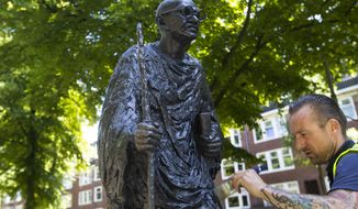 "A worker applied a coat of wax to the bronze statue of Mahatma Gandhi after removing red paint in Amsterdam Wednesday, June 17, 2020. The statue was daubed in red paint and ""Racist"" was written on its base, an apparent reference to Gandhi's racist controversial references to Africans in his writings, amid a wave of attacks on statues of historical figures in the United States and Europe. The death of George Floyd at the hands of Minneapolis police officers has sparked a reexamination of many countries' colonial histories and actions that often were exalted in the form of statues and other memorials. (AP Photo/Peter Dejong) ** FILE **"