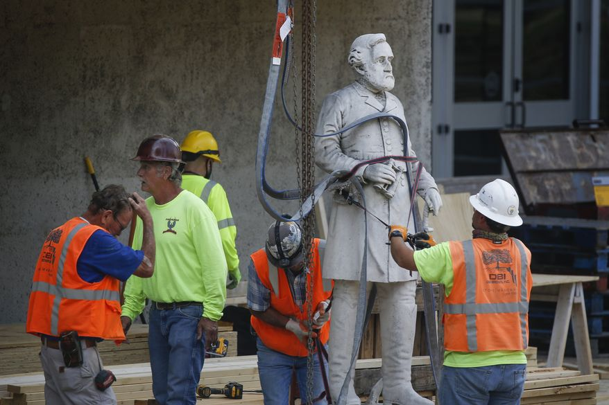 Construction workers move a statue of Confederate Gen. Robert E. Lee as they begin the removal of the Confederate War Memorial at Pioneer Park on Monday, June 22, 2020, in downtown Dallas. (Ryan Michalesko/The Dallas Morning News via AP)