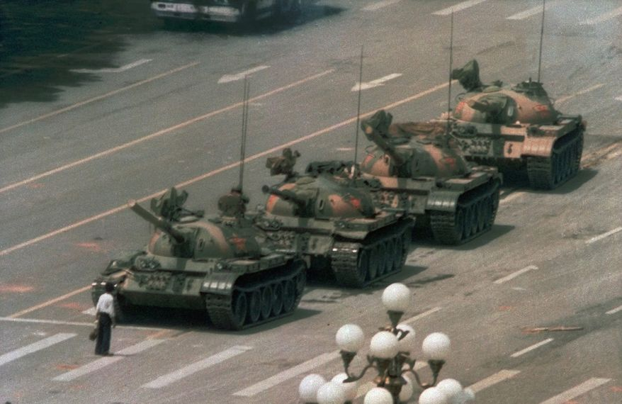 """A Chinese man stands alone to block a line of tanks heading east on Beijing's Cangan Blvd. in Tiananmen Square on June 5, 1989.  The man, calling for an end to the recent violence and bloodshed against pro-democracy demonstrators, was pulled away by bystanders, and the tanks continued on their way.  The Chinese government crushed a student-led demonstration for democratic reform and against government corruption, killing hundreds, or perhaps thousands of demonstrators in the strongest anti-government protest since the 1949 revolution. Ironically, the name Tiananmen means """"Gate of Heavenly Peace"""". (AP Photo/Jeff Widener)"""