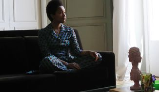 In this photo taken on Tuesday, June 16, 2020, American content creator Tamu McPherson sits on the sofa at her home in Milan, Italy. The U.S protests against systemic racism, which are spreading around the globe, are now putting the spotlight on the fashion world in its role as a cultural beacon, and emboldening insiders  -- some with lucrative deals that often assume their discretion -- to speak up.  (AP Photo/Antonio Calanni)