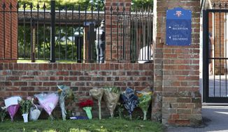 Flower tributes at the entrance to Holt School in Wokingham, England, in memory of teacher James Furlong, a victim of a terror attack in nearby Reading, Monday June 22, 2020.  A lone terror suspect remains in custody accused of killing three people and wounding three others in a Reading park on Saturday night. (Steve Parsons/PA via AP)