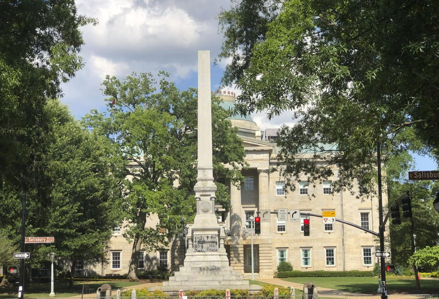 An obelisk memorializing the U.S. Confederacy located on the grounds of the North Carolina Capitol remains partially intact Monday afternoon, June 22, 2020, in Raleigh, N.C. Crews have not yet fully removed the statue. (AP Photo/Bryan Anderson)