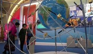 FILE - In this Oct. 19, 2017, file photo, visitors look at a display of satellite technologies at an exhibition highlighting China's achievements under five years of President Xi Jinping's leadership at the Beijing Exhibition Hall in Beijing. China on Tuesday, June 23, 2020 launched the final satellite in its Beidou constellation that emulates the U.S. Global Positioning System, marking a further step in the country's advance as a major space power. (AP Photo/Ng Han Guan, File)