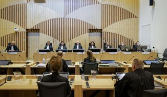 Presiding judge Hendrik Steenhuis, rear, fourth from left, opens the court session as the trial resumed at the high security court building at Schiphol Airport, near Amsterdam, Monday, June 8, 2020, for three Russians and a Ukrainian charged with crimes including murder for their alleged roles in the shooting down of Malaysia Airlines Flight MH17 over eastern Ukraine nearly six years ago. (AP Photo/Robin van Lonkhuijsen, POOL)