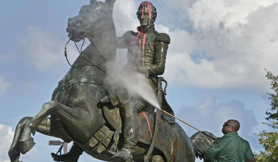 In this file photo, Ronnie English, a City of Jacksonville worker, pressure-washes the statue of Andrew Jackson after it was defaced with paint Monday, June 22, 2020, in downtown Jacksonville, Fla. (Will Dickey/The Florida Times-Union via AP)  **FILE**