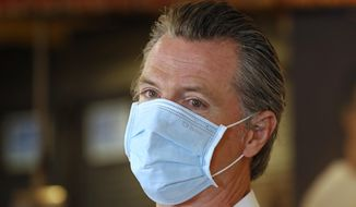 FILE - In this June 19, 2020, file photo, California Gov. Gavin Newsom, wears a face mask as he answers a reporter's question during his visit to the Queen Sheba Ethiopian Cuisine restaurant in Sacramento, Calif. Newsom implored people Monday, June 22, 2020, to wear face coverings to protect against the coronavirus and allow businesses to safely open after several days in which the state saw its highest virus hospitalizations and number of infections to date. (AP Photo/Rich Pedroncelli, Pool)