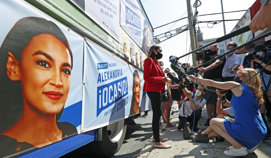U.S. Rep. Alexandria Ocasio-Cortez, D, New York, center, meets a cluster of media beside a campaign truck plastered with her promotional material in Astoria, Queens, Tuesday, June 23, 2020, on primary election day in New York. (AP Photo/Kathy Willens) ** FILE **