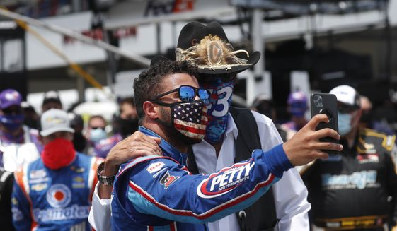 Team owner Richard Petty, right, poses for a selfie with driver Bubba Wallace prior to the start of the NASCAR Cup Series at the Talladega Superspeedway in Talladega, Ala., Monday, June 22, 2020. (AP Photo/John Bazemore)