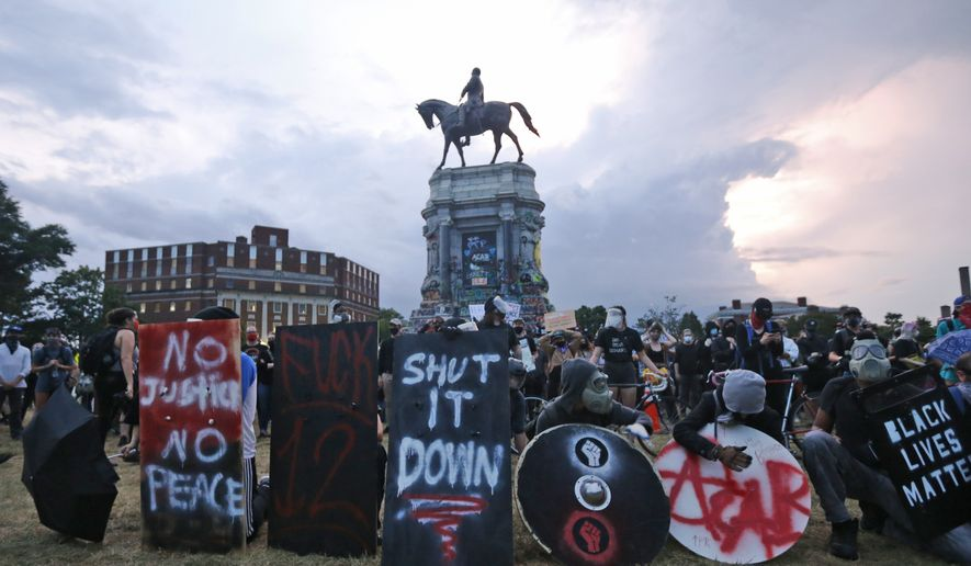 Protesters with shields and gas masks wait for police action as they surround the statue of Confederate Gen. Robert E. Lee on Monument Avenue, Tuesday, June 23, 2020, in Richmond, Va. The state has ordered the area around the statue closed from sunset to sunrise. (AP Photo/Steve Helber) ** FILE **