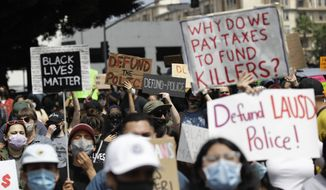 Demonstrators holds signs during a protest to demand the defunding of the Los Angeles school district police outside of the school board headquarters Tuesday, June 23, 2020, in Los Angeles. (AP Photo/Marcio Jose Sanchez) ** FILE **