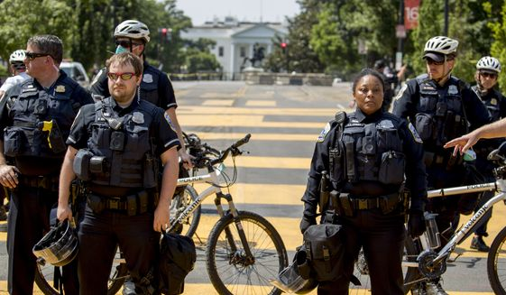 The White House is visible as a line of police officers close 16th Street Northwest between H and I Street renamed Black Lives Matter Plaza, Tuesday, June 23, 2020, in Washington. (AP Photo/Andrew Harnik)